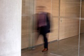 Photo of Blurry man walking out of glass doors