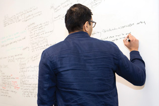 Photo of a student writing on a white board