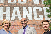 "Three people posing for a photo in front of a brick wall with the words ""you've changed"""