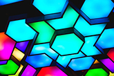 Abstract hexagon images backed by blue and turquoise lights.