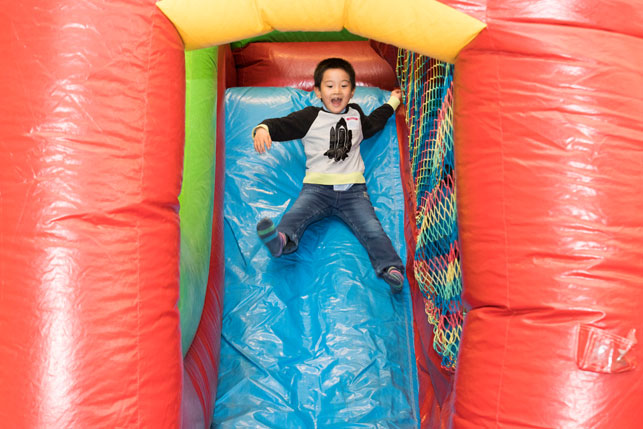 kid on bouncy castle slide